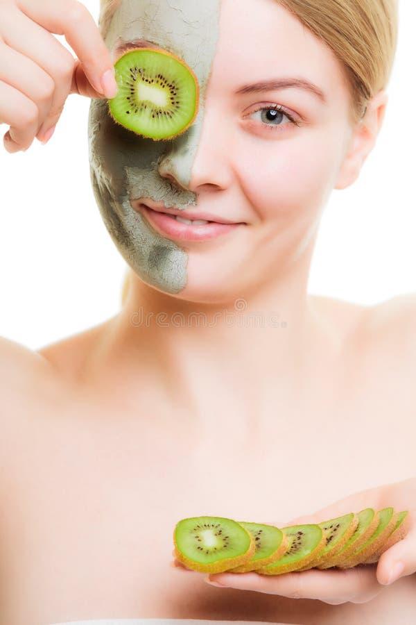Donna nella maschera dell'argilla sull'occhio della copertura del fronte con il kiwi fotografie stock
