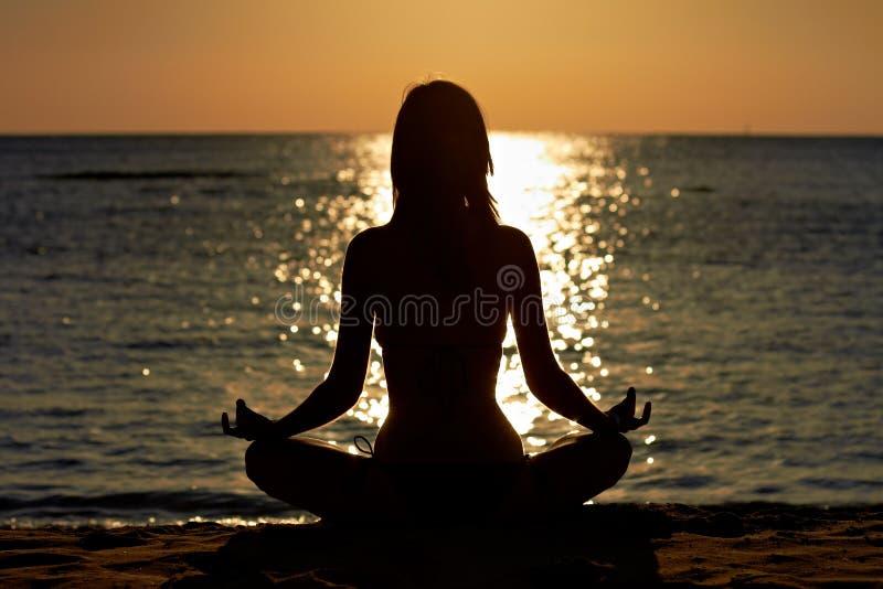Donna nella meditazione del loto di yoga alla spiaggia immagini stock libere da diritti