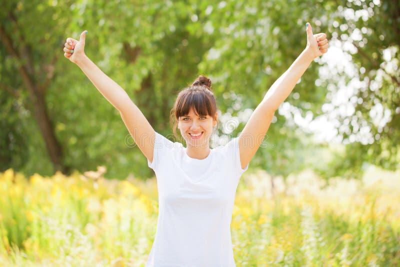 Donna nella mostra bianca della maglietta pollici su immagini stock