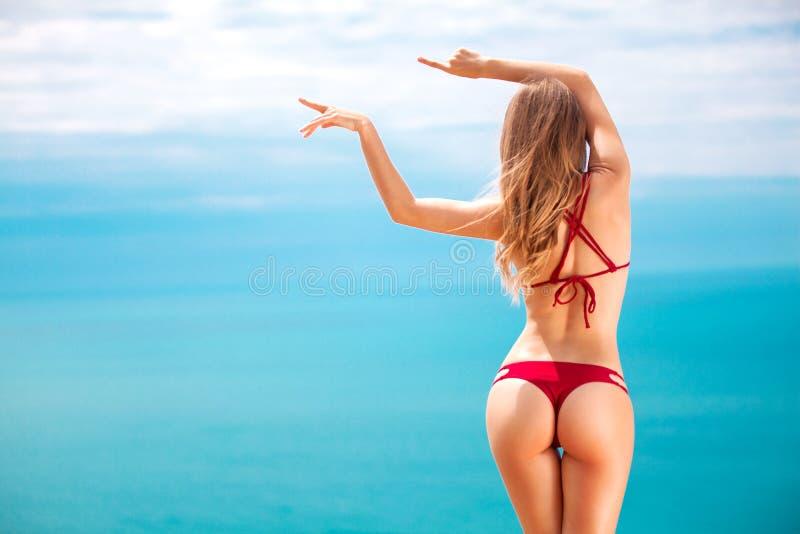 Donna nella nuotata che posa sulla spiaggia sopra il fondo del mare all'estate che indica sullo spazio della copia fotografia stock