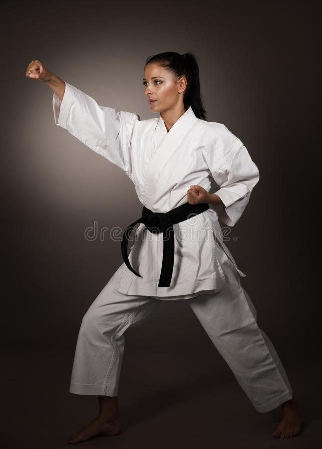 Donna nella perforazione bianca del kimono duro nell'aero- una ragazza di arte marziale di karatè fotografie stock libere da diritti