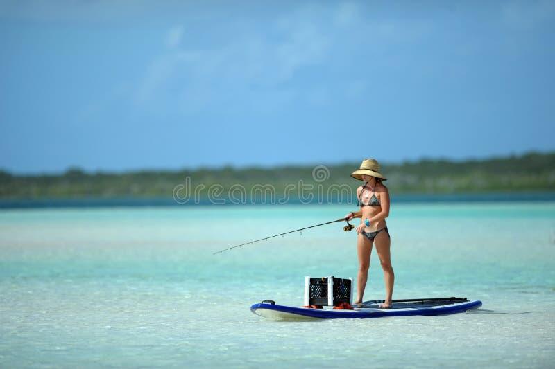 Donna nella pesca del bikini e nell'imbarco della pala fotografie stock libere da diritti
