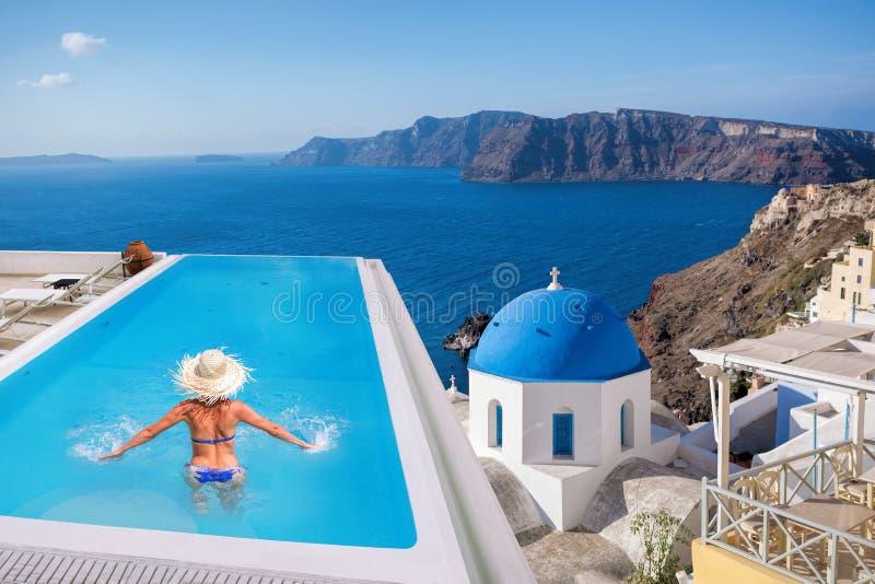 Donna nella piscina, villaggio di OIA sull'isola di Santorini, Grecia fotografie stock