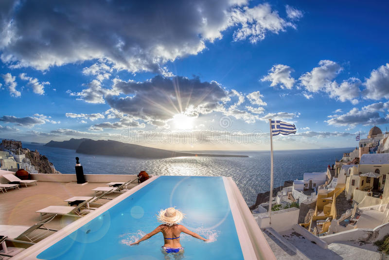Donna nella piscina, villaggio di OIA sull'isola di Santorini, Grecia fotografia stock