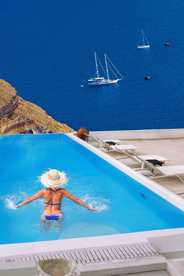 Donna nella piscina, villaggio di OIA sull'isola di Santorini, Grecia fotografie stock libere da diritti