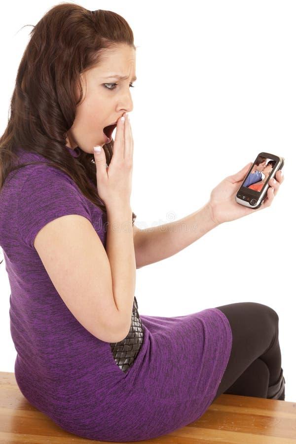 Donna nella porpora indietro scossa allo schermo del telefono immagini stock libere da diritti
