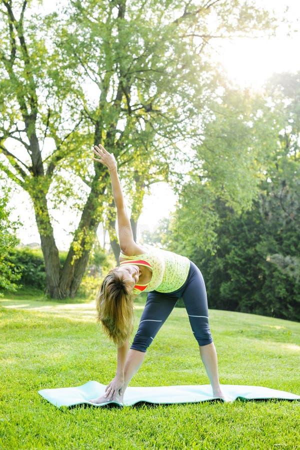 Donna nella posa del triangolo di yoga immagine stock libera da diritti
