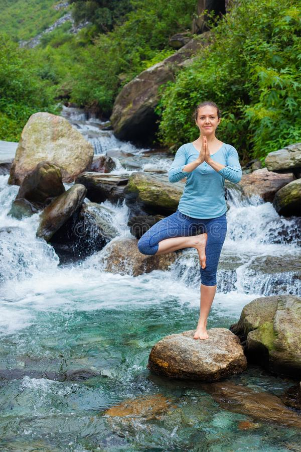Donna nella posa dell'albero di Vrikshasana di asana di yoga alla cascata all'aperto fotografia stock libera da diritti