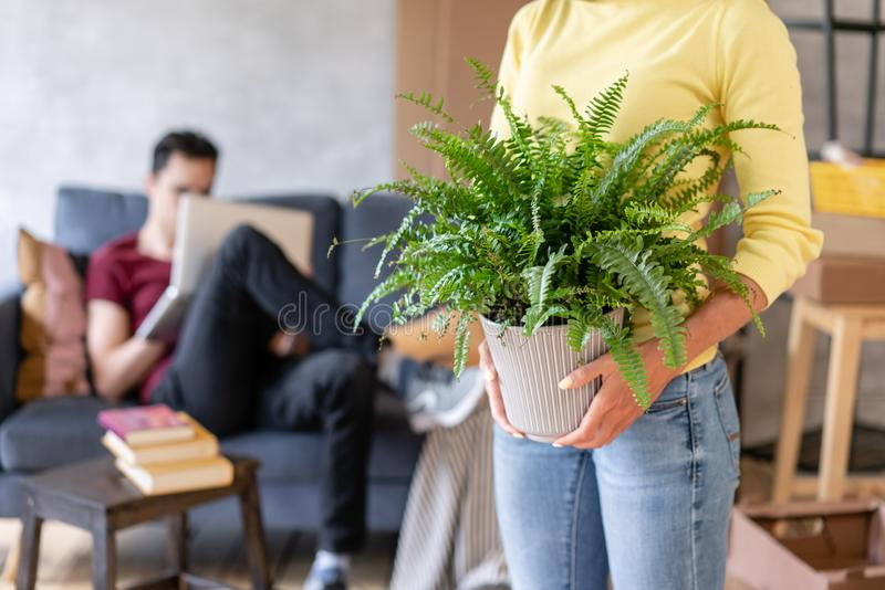 Donna nella priorità alta che tiene un fiore della felce in sue mani Giovani coppie che avvicinano verso un nuovo appartamento ri immagini stock libere da diritti