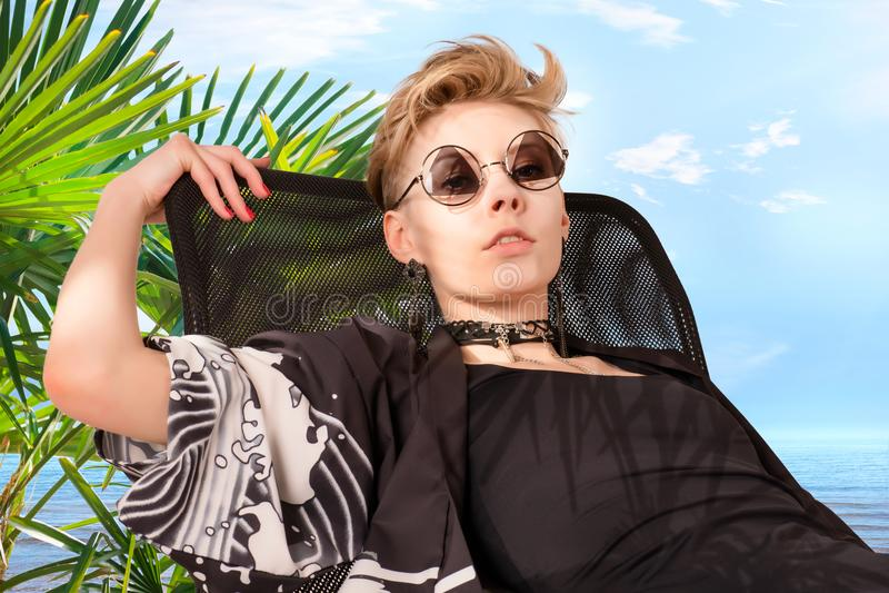 Donna nella sedia contro le palme e la costa di mare immagini stock