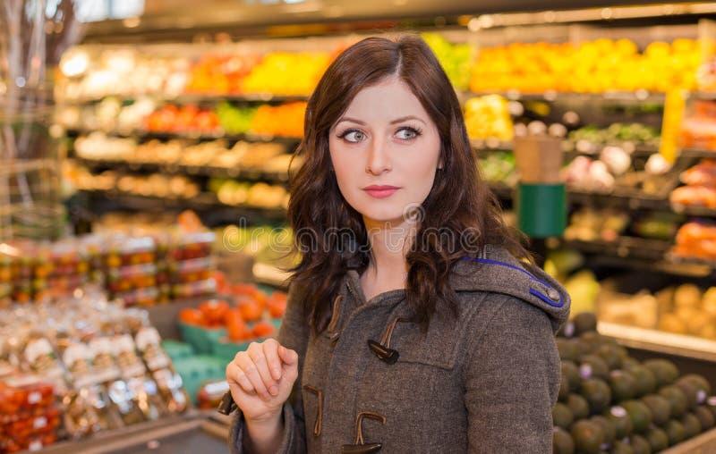 Donna nella sezione dei prodotti di una drogheria fotografia stock