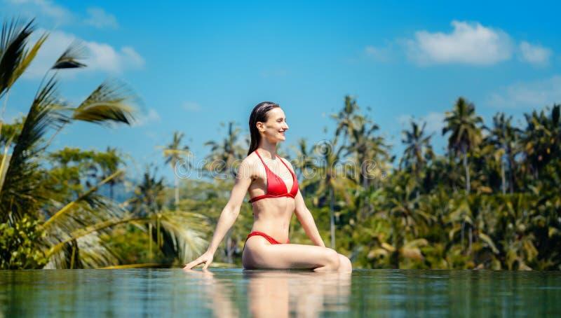 Donna nella vacanza tropicale che si siede nell'acqua dello stagno fotografie stock