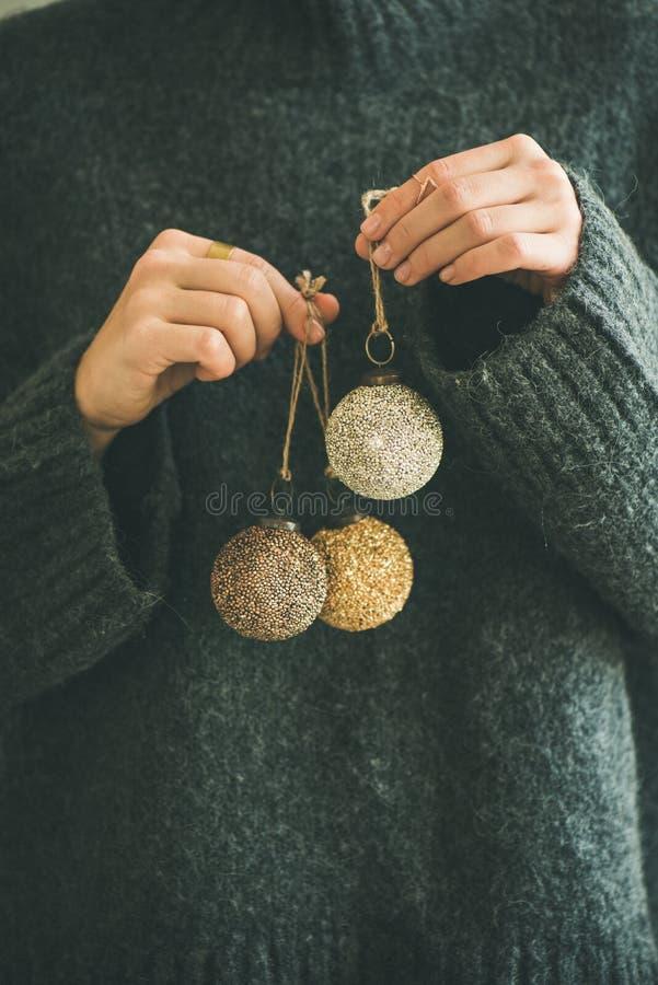 Donna nelle palle dorate e d'argento grige della tenuta del maglione immagini stock libere da diritti