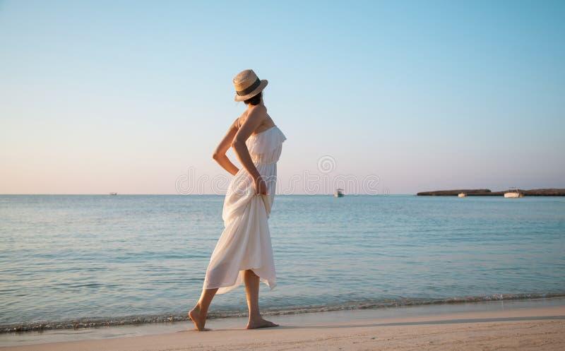 Donna nelle prendisole bianche che cammina dalla spiaggia fotografie stock