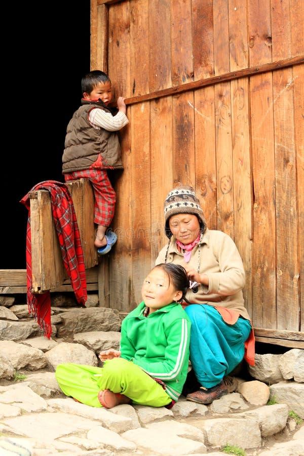 Donna nepalese con i suoi bambini vicino alla casa immagine stock libera da diritti