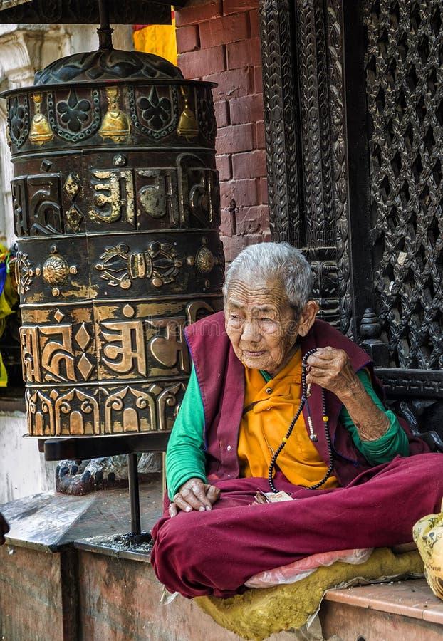 Donna nepalese non identificata che prega e che medita intorno al santuario buddista Boudhanath Stupa, Kathmandu, Nepal dell'attr fotografie stock