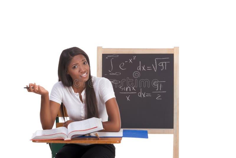 Donna nera dello studente di college che studia l'esame di per la matematica fotografia stock