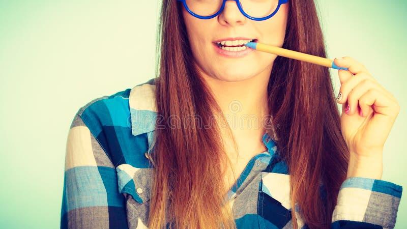 Donna nerd felice nella penna di tenuta di vetro fotografia stock libera da diritti