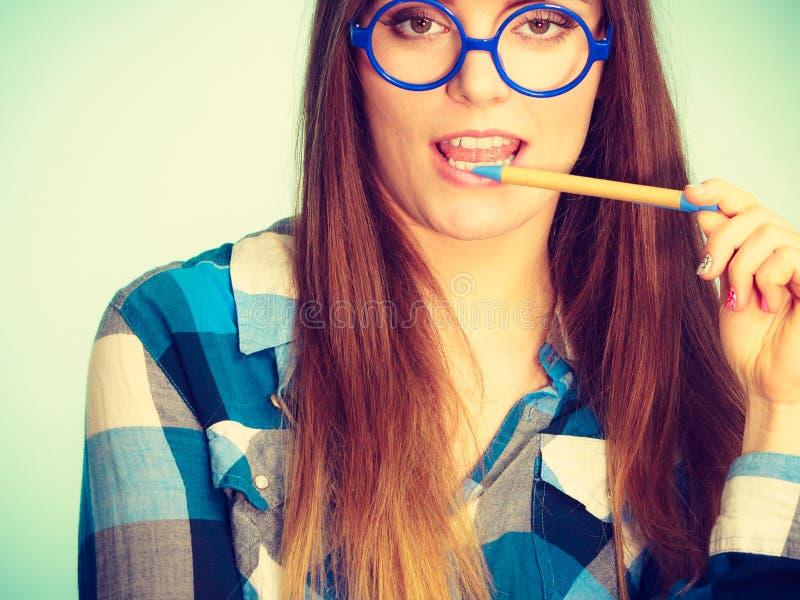 Donna nerd strana nella penna di tenuta di vetro fotografia stock libera da diritti