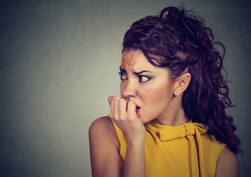 Donna nervosa spaventata che morde le sue unghie ansiose fotografia stock libera da diritti