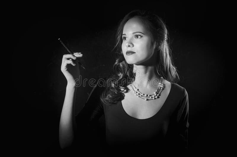 Donna noir di stile del film in sigaretta della tenuta del vestito che sta di nuovo alla macchina fotografica Posa femminile con  immagine stock