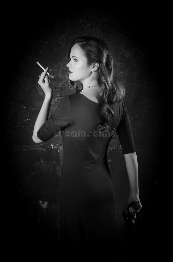 Donna noir di stile del film in sigaretta della tenuta del vestito che sta di nuovo alla macchina fotografica Posa femminile con  fotografie stock