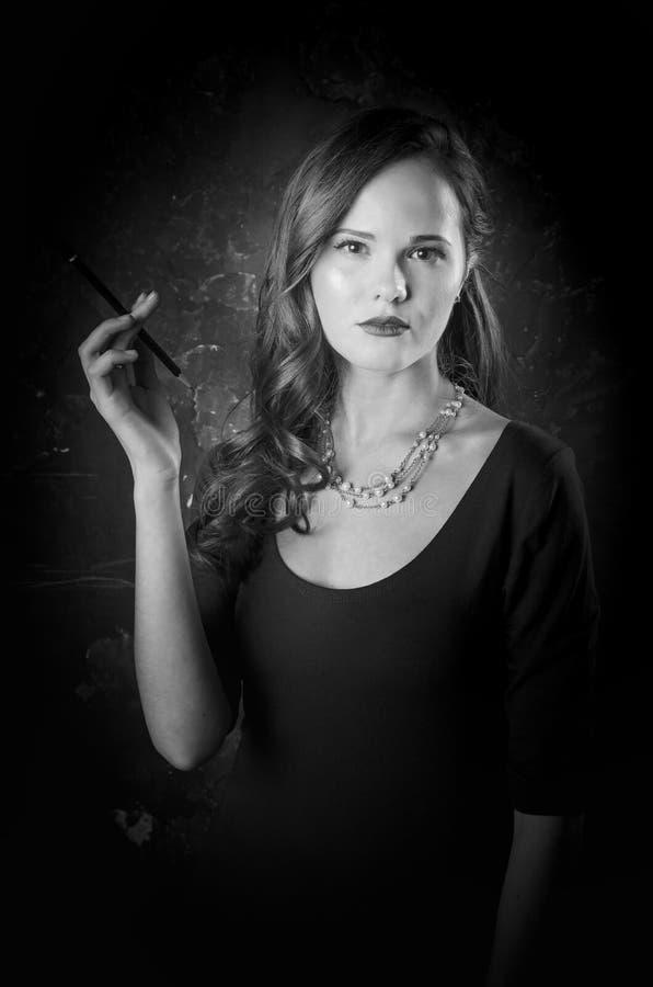Donna noir di stile del film in sigaretta della tenuta del vestito che sta di nuovo alla macchina fotografica Posa femminile con  immagine stock libera da diritti