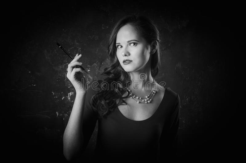 Donna noir di stile del film in sigaretta della tenuta del vestito che sta di nuovo alla macchina fotografica Posa femminile con  immagini stock libere da diritti