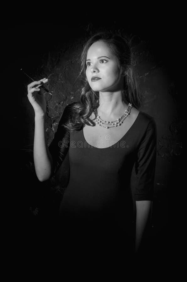 Donna noir di stile del film in sigaretta della tenuta del vestito Fotographia in bianco e nero Vecchia foto di modo fotografia stock libera da diritti
