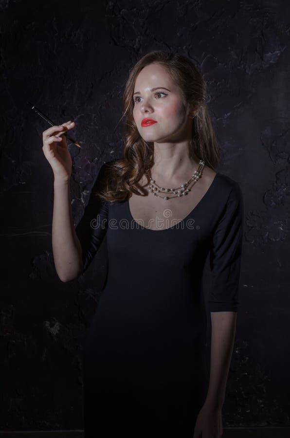 Donna noir di stile del film in sigaretta della tenuta del vestito Fotographia in bianco e nero Vecchia foto di modo immagine stock libera da diritti