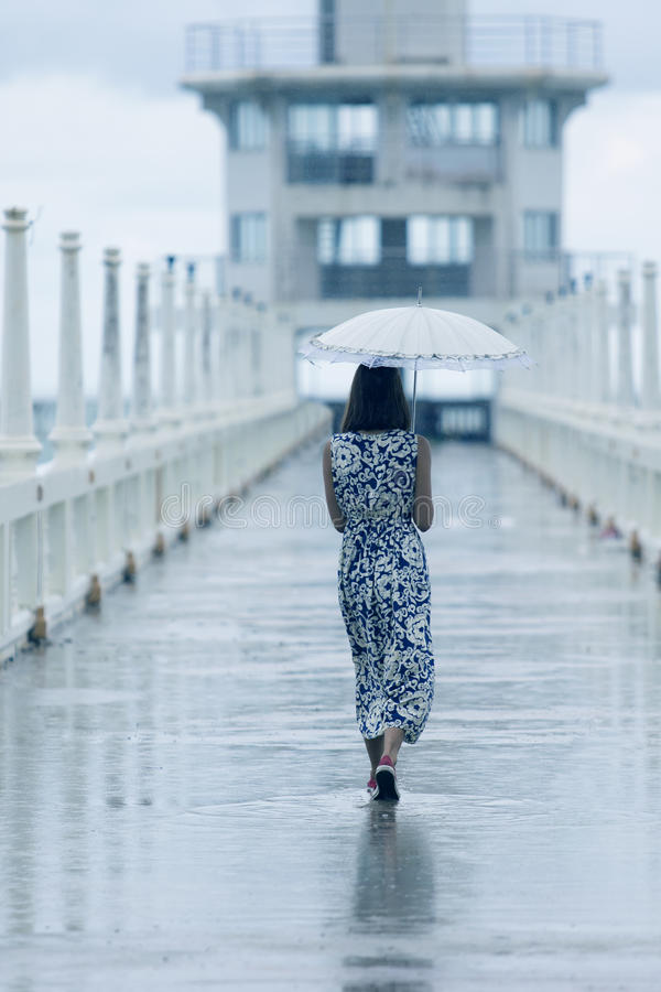Donna non-sposata che cammina sul modo con cadere della pioggia e dell'ombrello fotografia stock libera da diritti