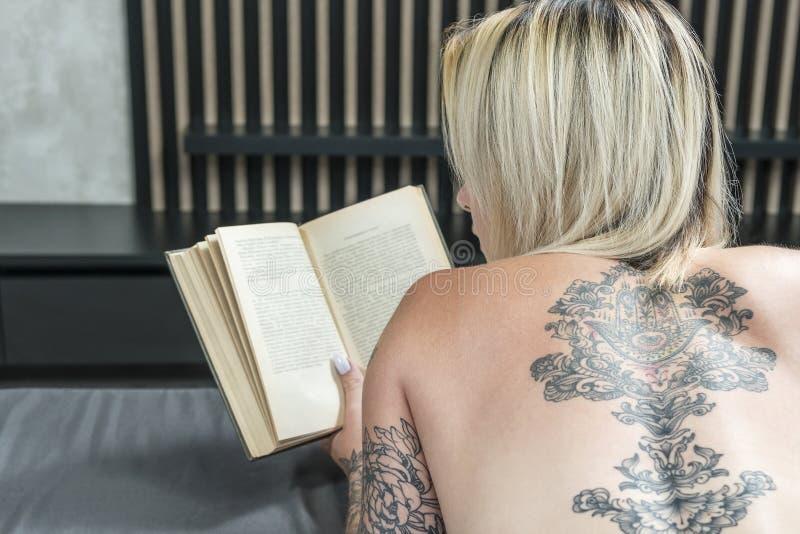 Donna nuda che legge un libro fotografia stock