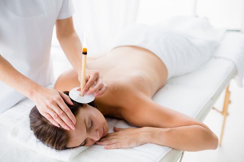Donna nuda che riceve trattamento della candela dell'orecchio dal massaggiatore immagine stock libera da diritti