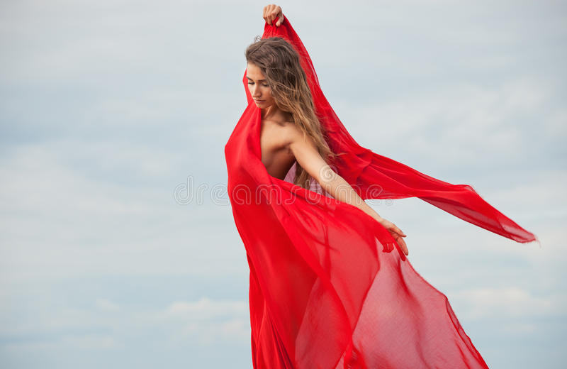 Donna nuda con tessuto rosso fotografie stock