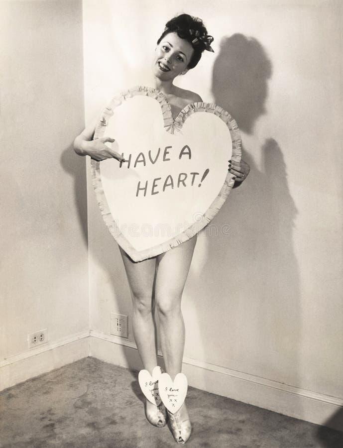 Donna nuda coperta da un segno in forma di cuore fotografie stock