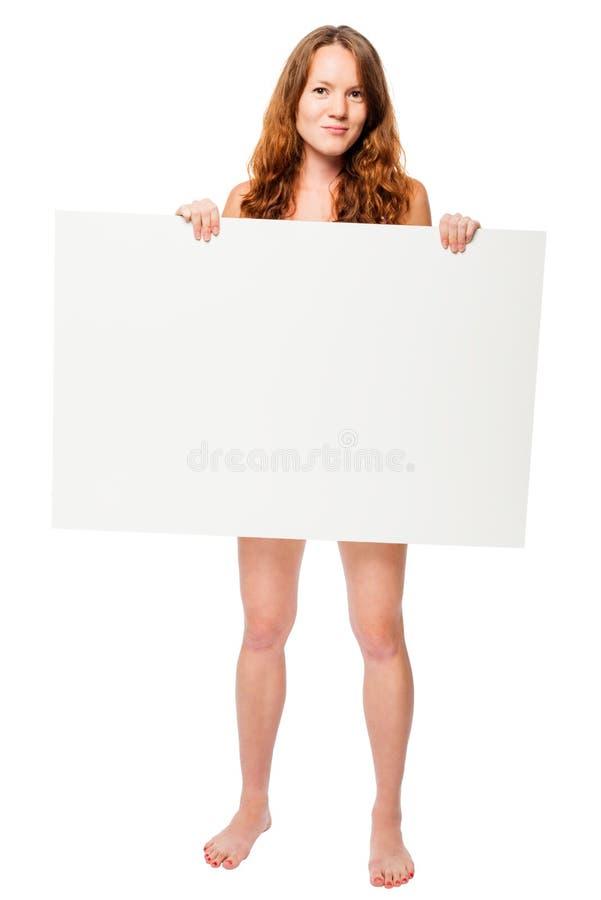 Donna nuda scalza che si nasconde dietro un tabellone per le affissioni bianco immagine stock