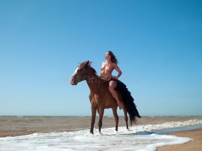 Donna nuda su a cavallo fotografia stock. Immagine di