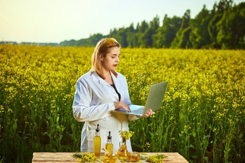 Donna o agricoltore dell'agronomo esaminare il giacimento sbocciante del canola della violenza facendo uso del taccuino immagine stock