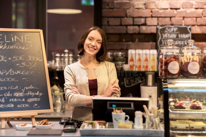 Donna o cameriera al banco felice al contatore del caffè fotografie stock libere da diritti