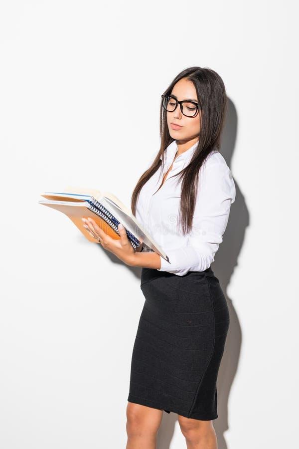 Donna o studente sorridente felice di affari in vestiti eleganti che tengono taccuino e penna su fondo bianco immagine stock