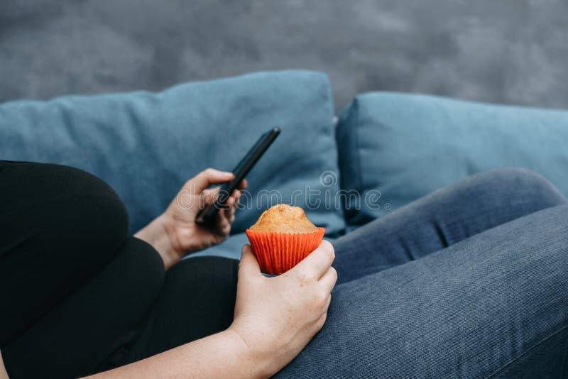 Donna obesa che mette su sofà che mangia i dolci fotografia stock libera da diritti