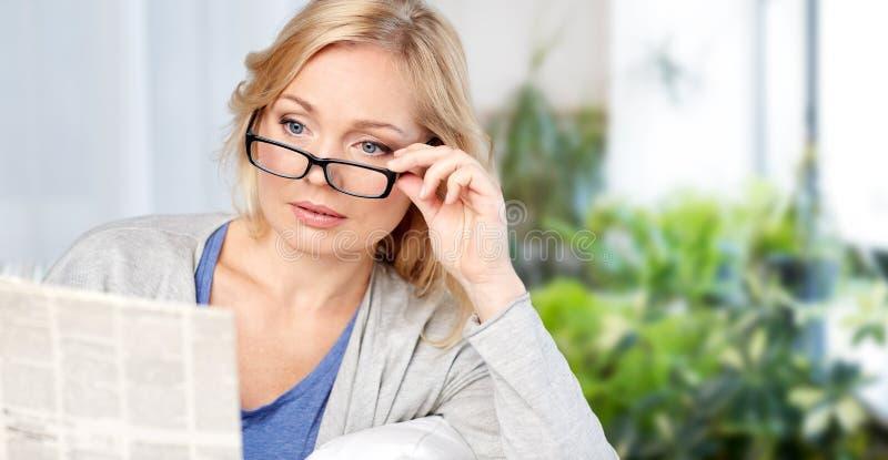 Donna in occhiali che legge giornale a casa fotografie stock