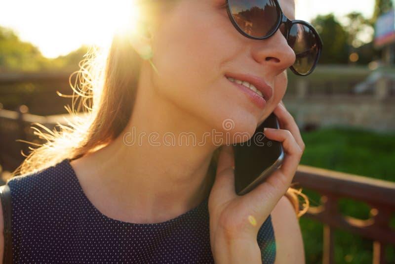 Donna in occhiali da sole che parla sullo smartphone mentre camminando giù fotografia stock
