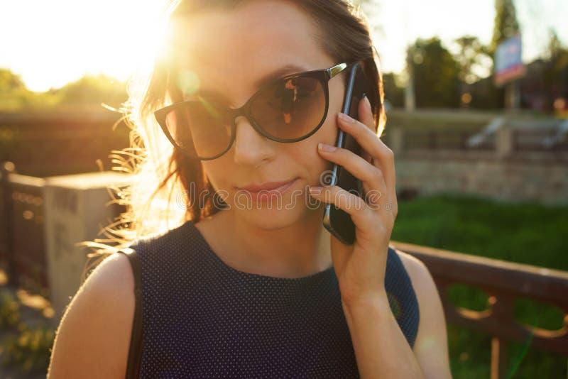 Donna in occhiali da sole che parla sullo smartphone mentre camminando giù immagini stock