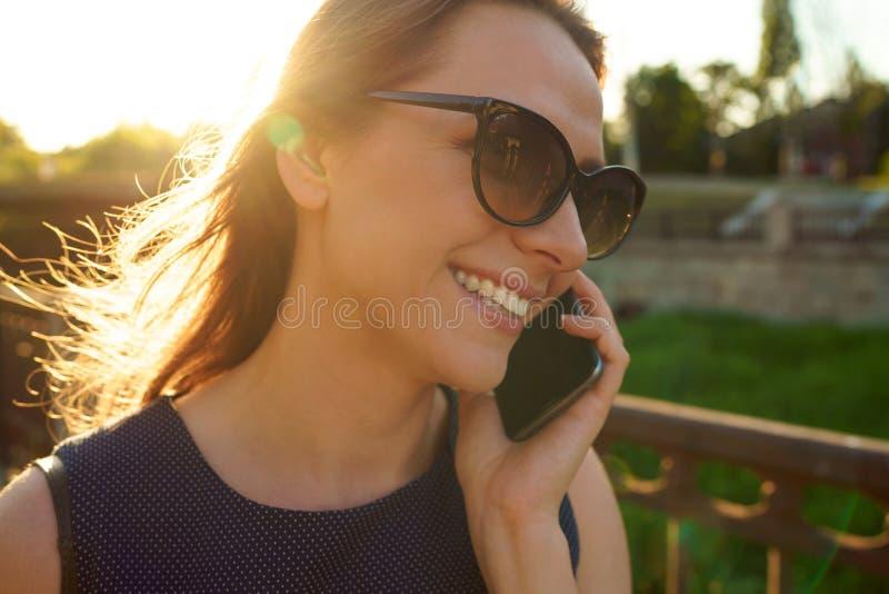 Donna in occhiali da sole che parla sullo smartphone mentre camminando giù fotografia stock libera da diritti