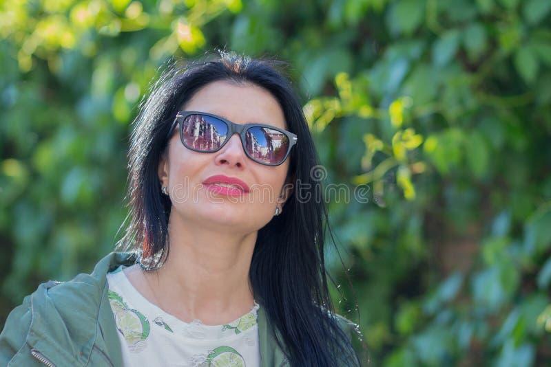 Donna in occhiali da sole e riflettere nella loro città fotografie stock libere da diritti