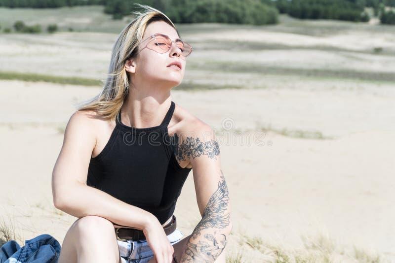 Donna in occhiali da sole nell'ambito della luce solare fotografie stock libere da diritti
