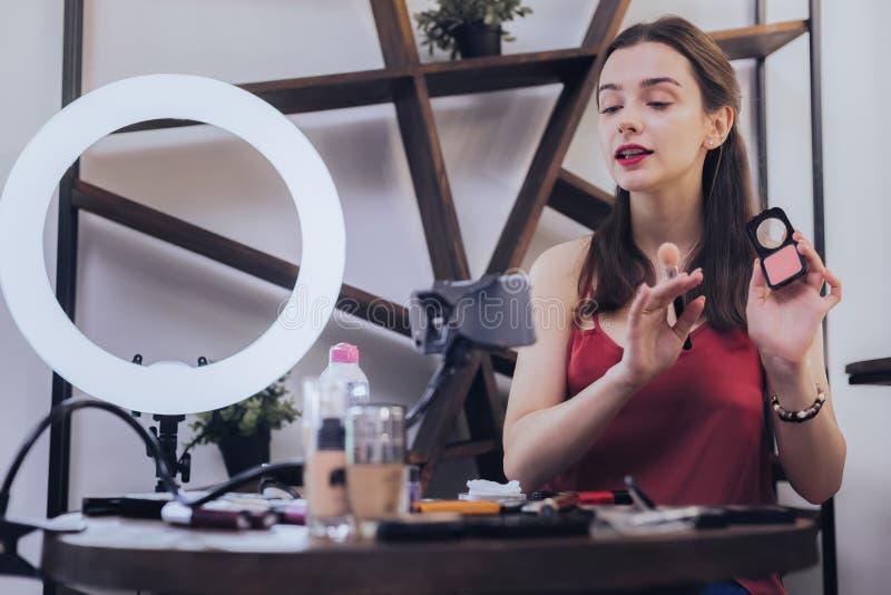 Donna occupata che usando la sua cipria mentre avendo video chiacchierata immagine stock libera da diritti