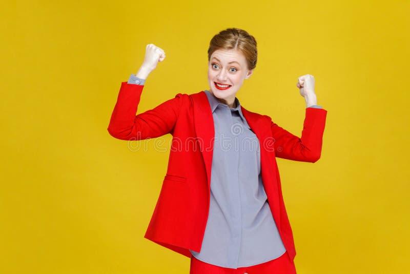 Donna ottimista di affari della testa di rosso di felicità nella vittoria rossa del vestito fotografia stock