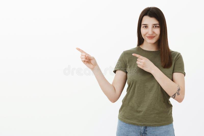 Donna ottimistica sicura ed ambiziosa con gli occhi marroni e sorridere dei capelli sicuro di sé ed osare come indicare sinistro  immagine stock